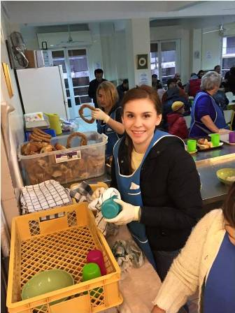 Hellenic American University student volunteering at a relief organization's soup kitchen.